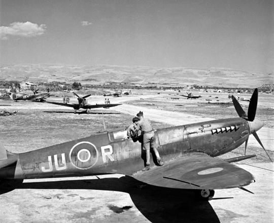 Myśliwce Spitfire z 111. Sqn RAF na lotnisku w Comiso; na pierwszym planie Mk IX, w tle starsze MkV (z trójłopatowymi śmigłami).