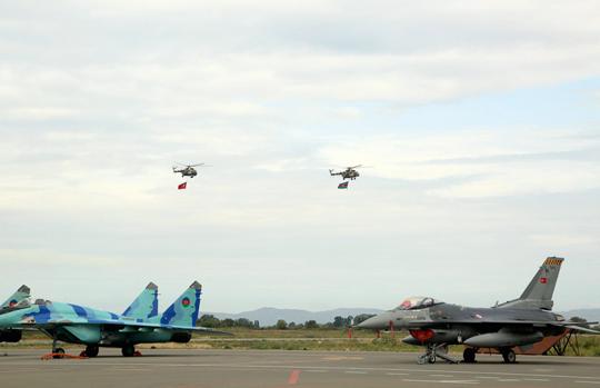 """Symboliczne zdjęcie zćwiczeń """"TurAz Qartali-2019"""" – po lewej azerski MiG-29 po prawej turecki F-16, w tle – śmigłowce w przelocie z flagami narodowymi."""