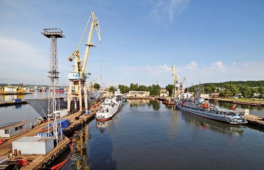Wstoczni trwają jeszcze prace przy fregacie rakietowej ORP Gen. T. Kościuszko (zlewej), okręcie ratowniczym  ORP Piast (zprawej), jak też okręcie hydrograficznym ORP Arctowski i50-letniej stacji demagnetyzacyjnej SD-11 (obydwie jednostki poza kadrem).